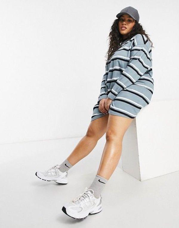 A model wearing a plus-size t-shirt dress in blue stripe.