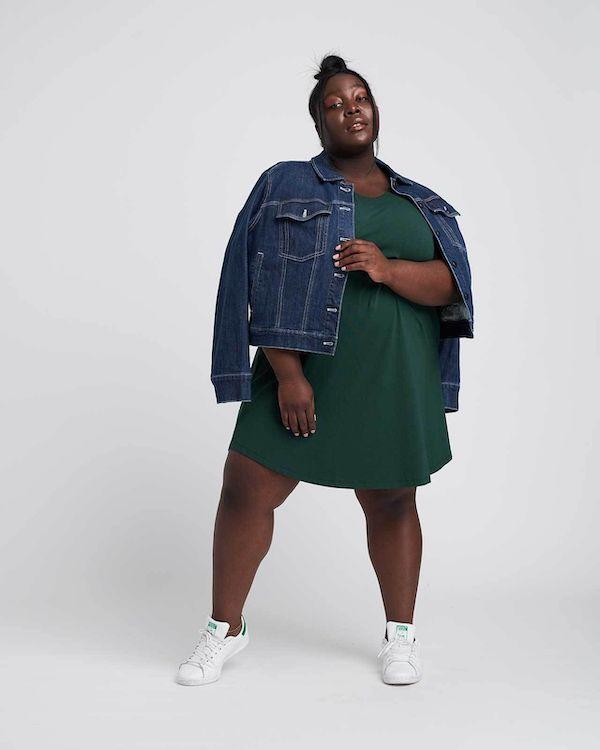 A model wearing a plus-size t-shirt dress in dark green.