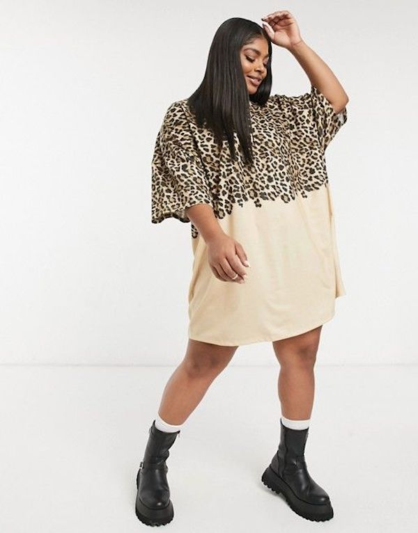A model wearing a plus-size t-shirt dress in cream and leopard print.