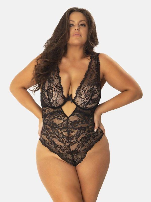A model wearing a plus-size lingerie teddy in black.