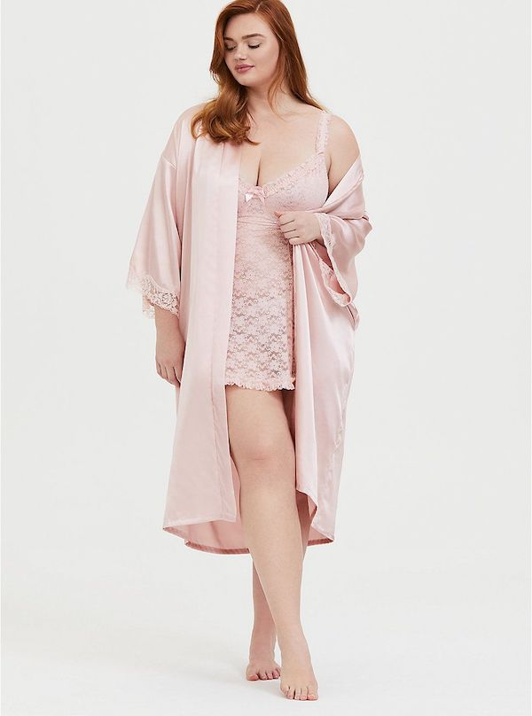 A model wearing a plus-size pink satin robe.