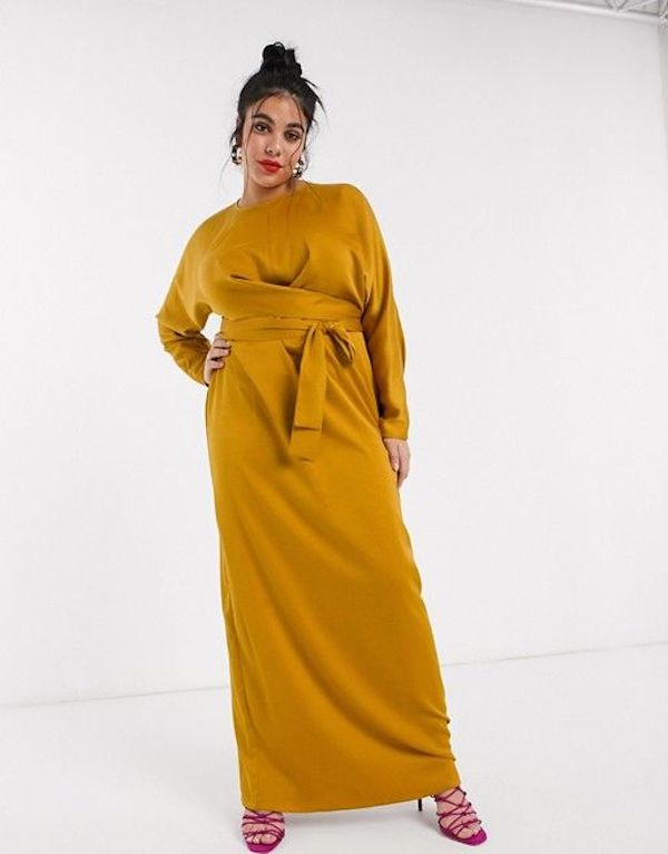 A model wearing a plus-size maxi dress in mustard.