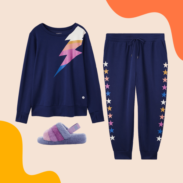 A navy sweatshirt with a lightening bolt, navy sweatpants with colorful stars, and multi-color slide slippers.