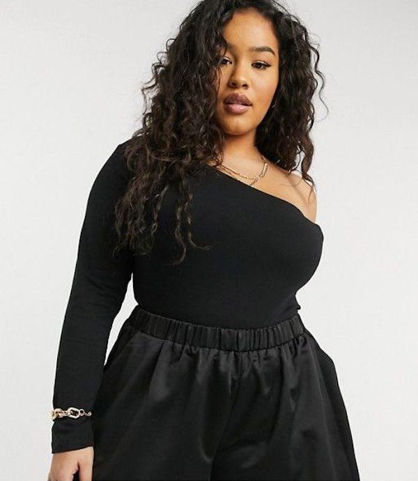 A model wearing a plus-size asymmetric top in black.
