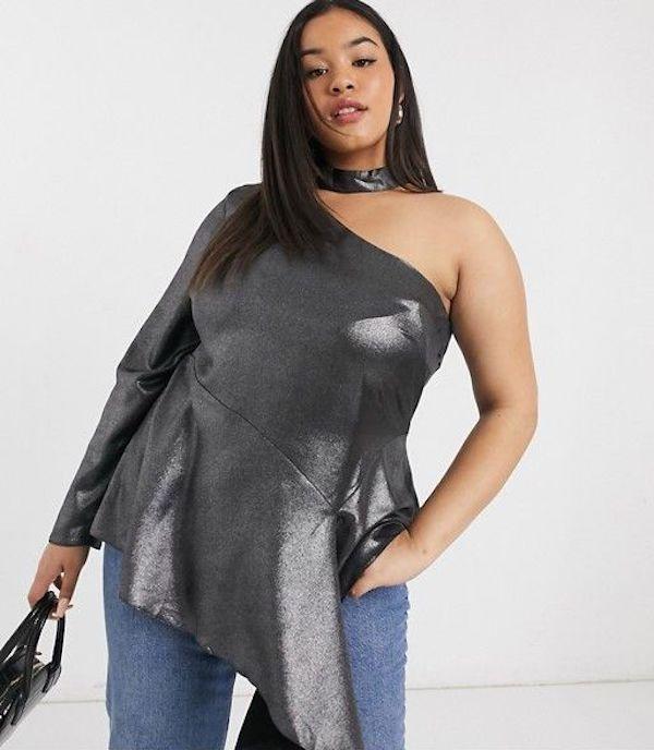 A model wearing a plus-size asymmetric top in charcoal gray.