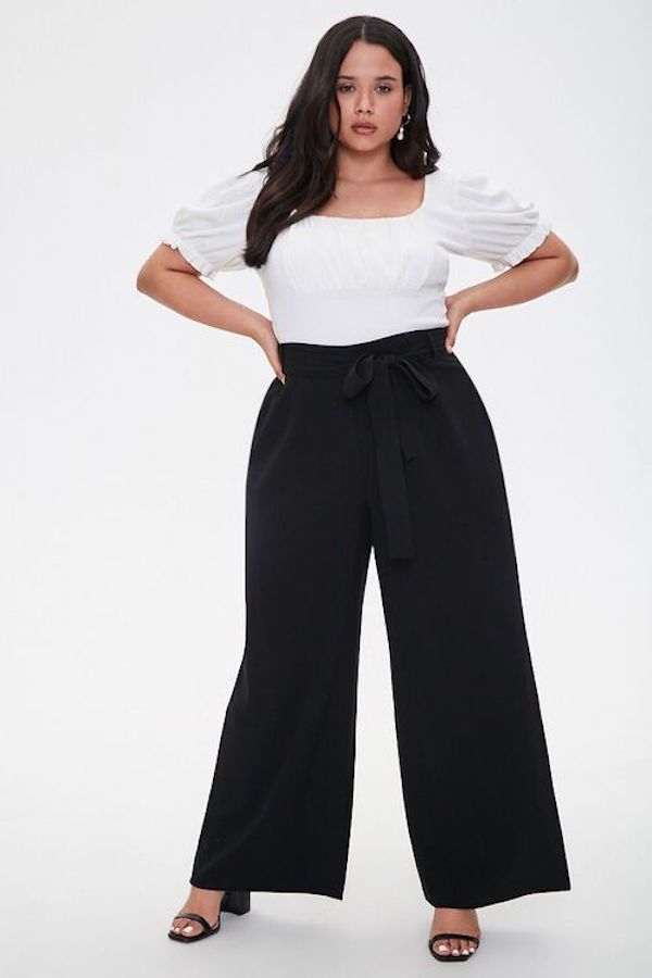 A model wearing plus-size beach pants in black.
