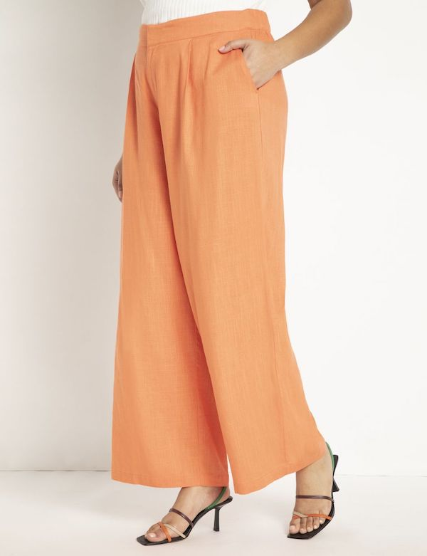 A model wearing plus-size beach pants in orange.