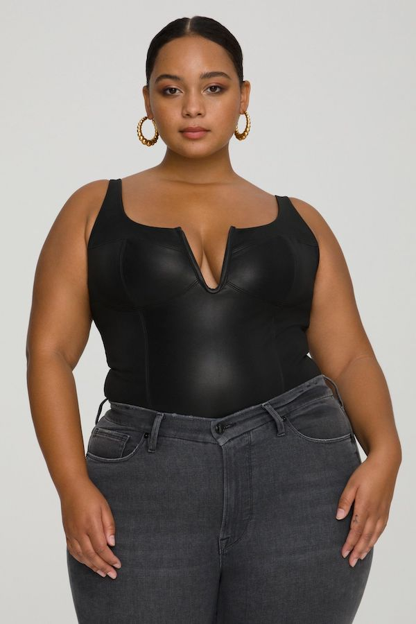 A model wearing a plus-size bustier top in black.