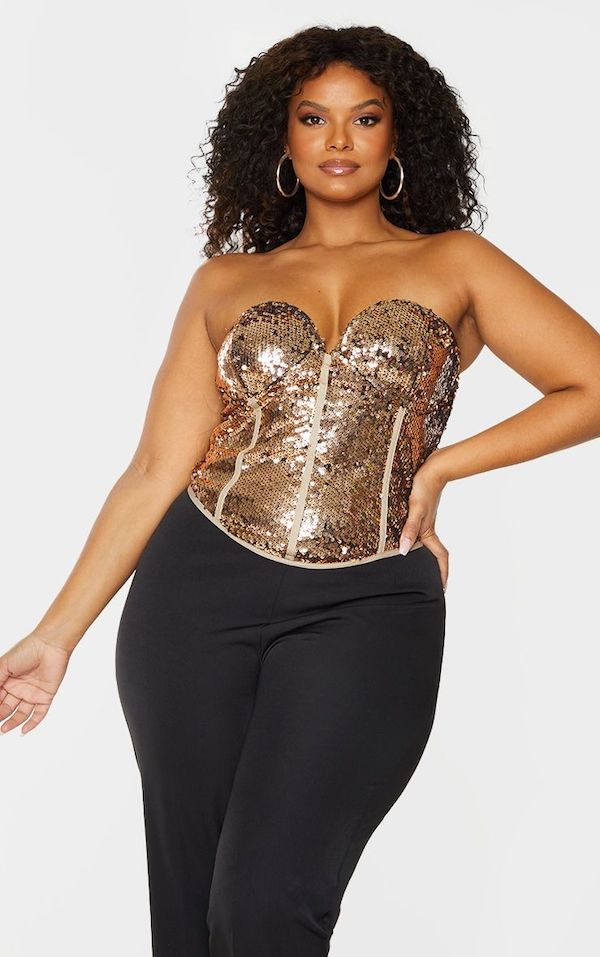 A model wearing a plus-size bustier top in gold.