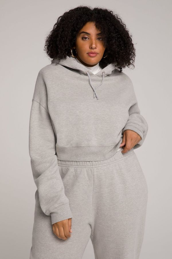 A model wearing a plus-size cropped hoodie in gray.