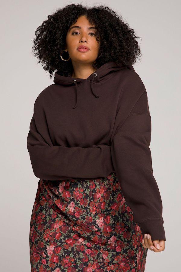 A model wearing a plus-size cropped hoodie in dark brown.