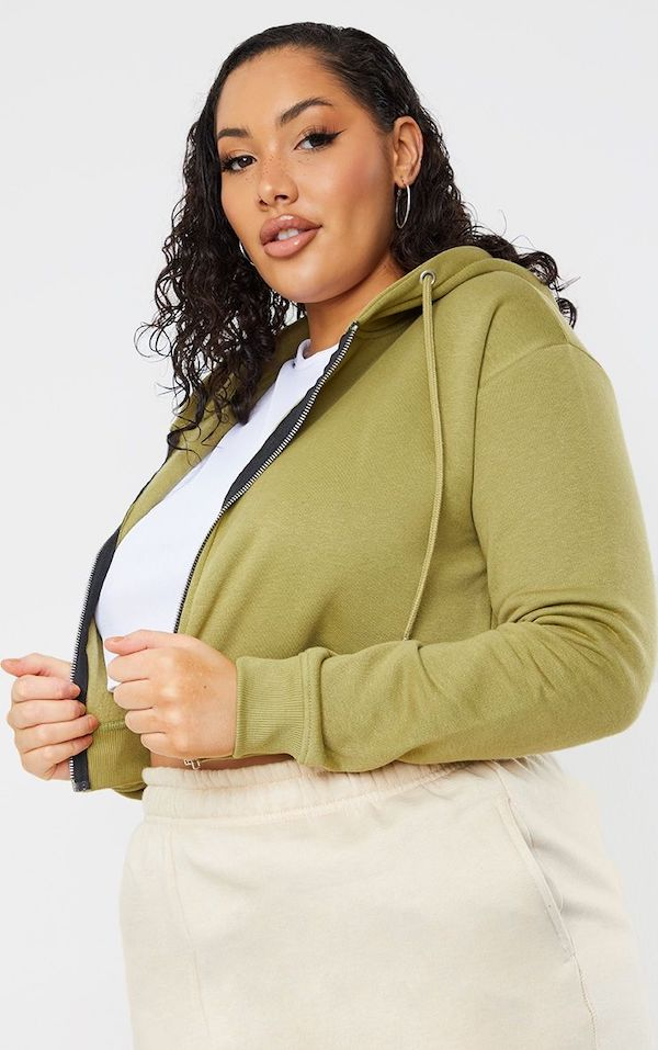 A model wearing a plus-size cropped hoodie in green.
