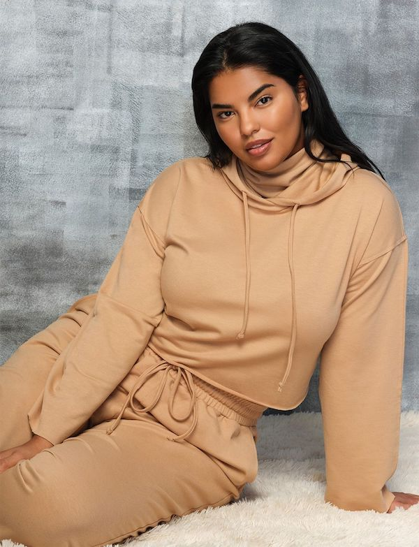 A model wearing a plus-size cropped hoodie in light brown.