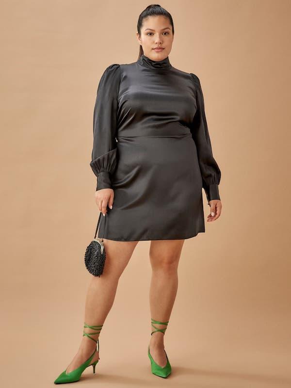 A model wearing a plus-size mini dress in black.