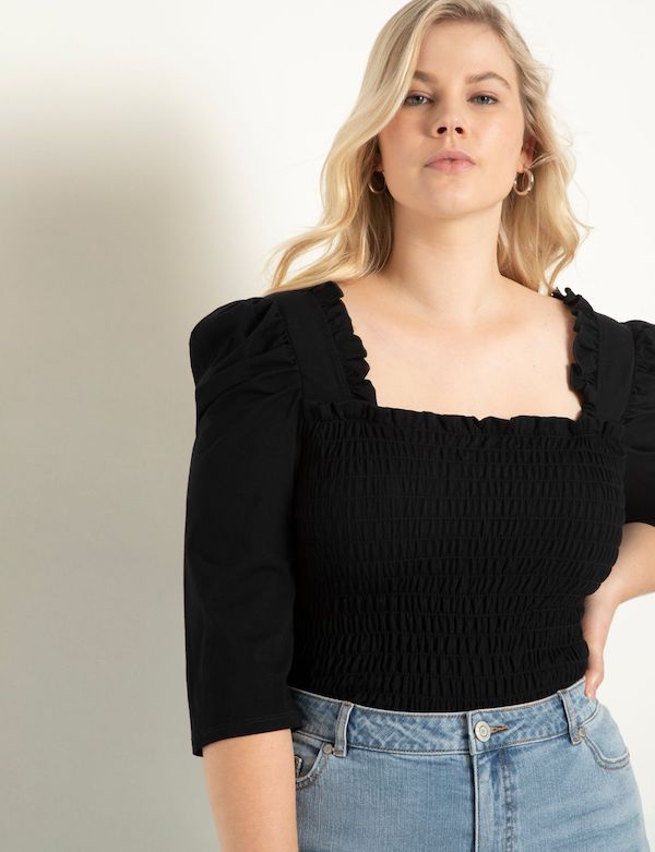 A model wearing a plus-size top in black.