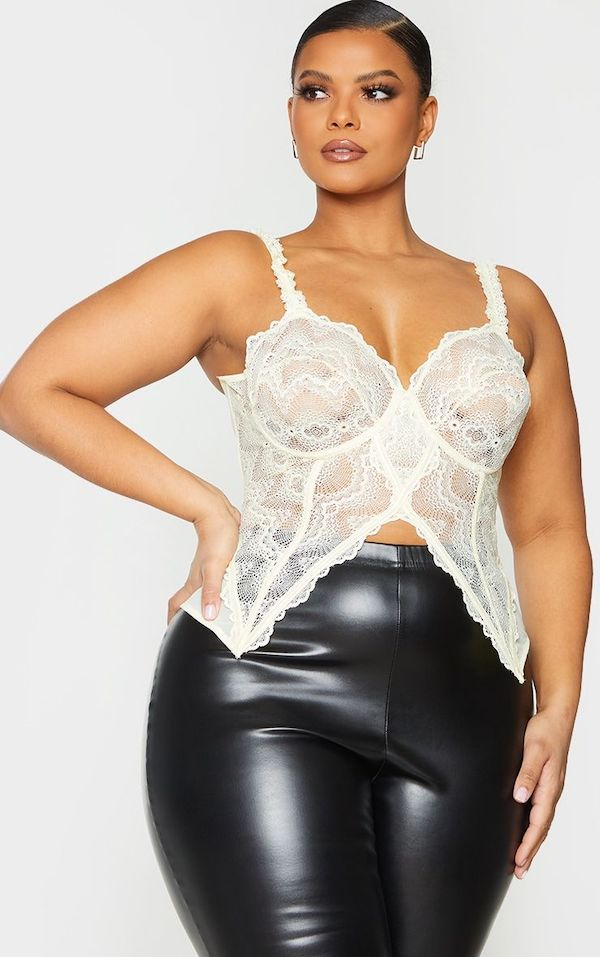 A model wearing a plus-size top in white lace.