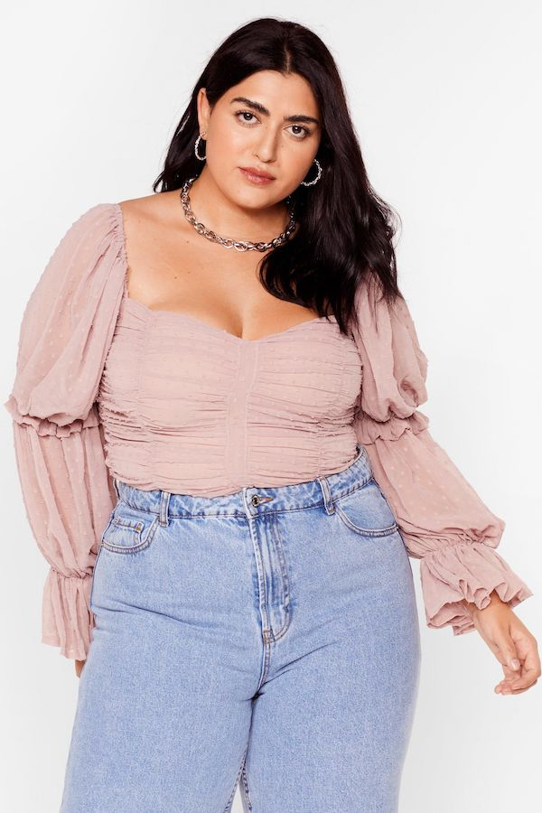 A model wearing a plus-size top in pink.