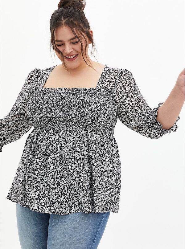A model wearing a plus-size floral top.