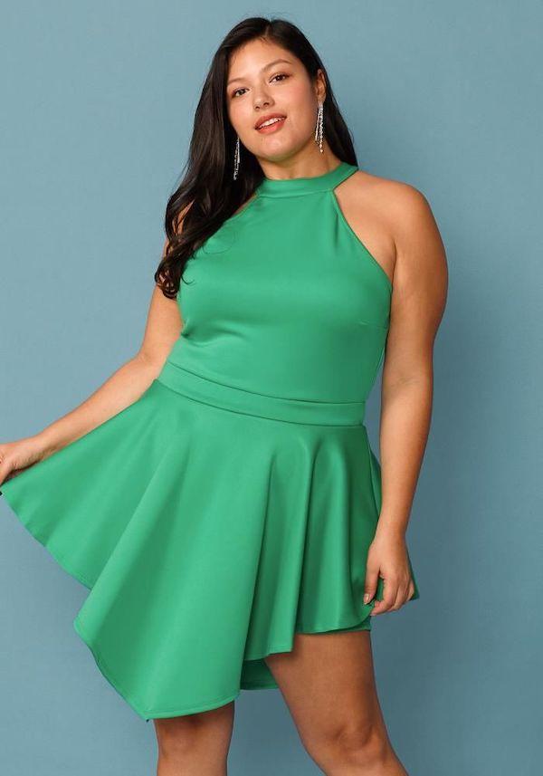 A model wearing a plus-size halter dress in green.