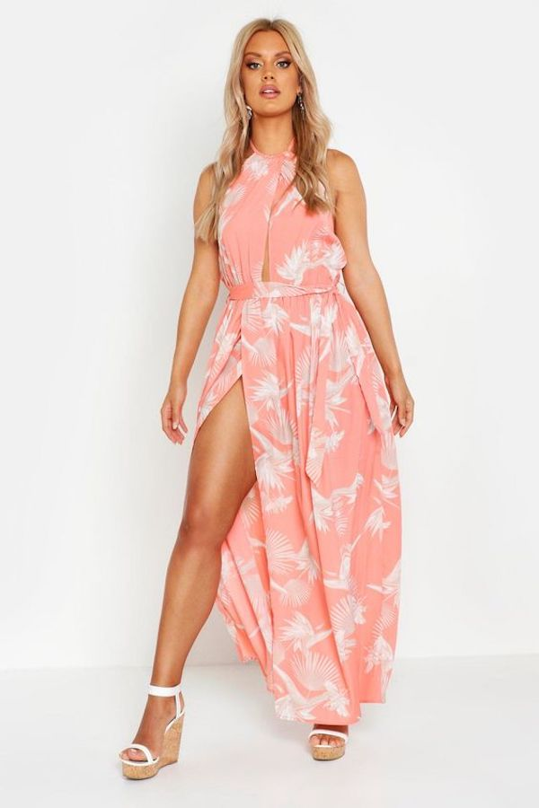A model wearing a plus-size halter dress in pink floral.