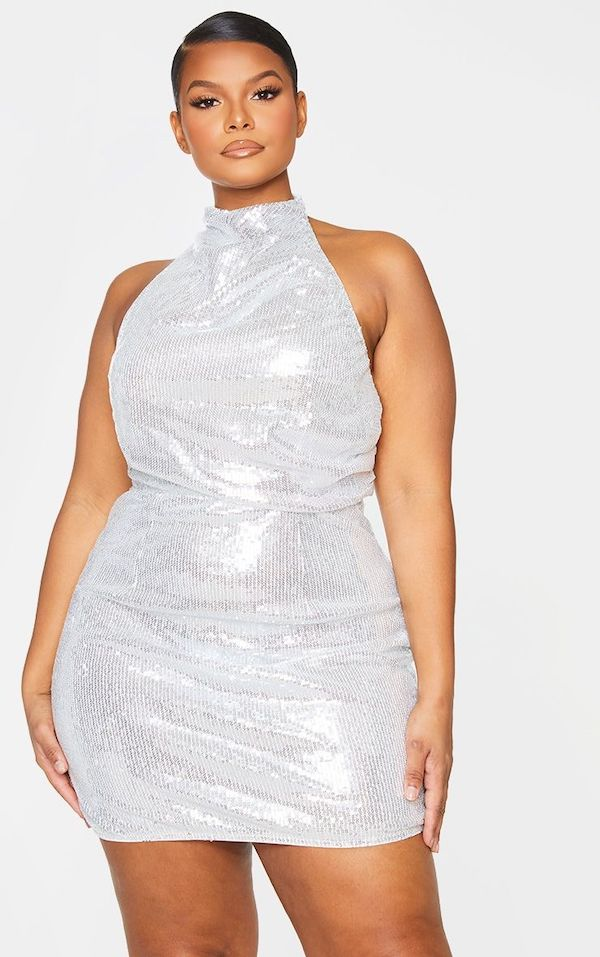 A model wearing a plus-size halter dress in silver.