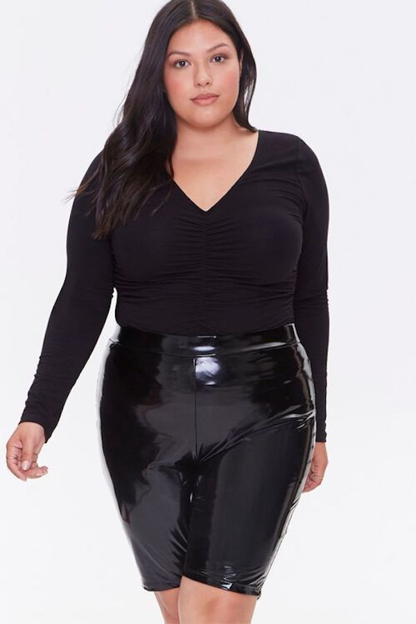 A model wearing plus-size leather shorts in black.