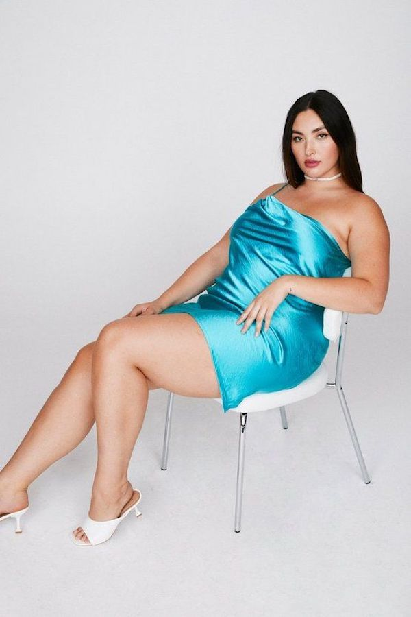 A model wearing a plus-size one-shoulder dress in teal.
