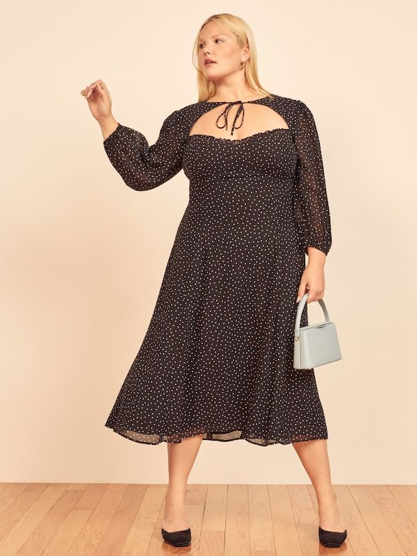 A model wearing a plus-size polka dot dress in black.