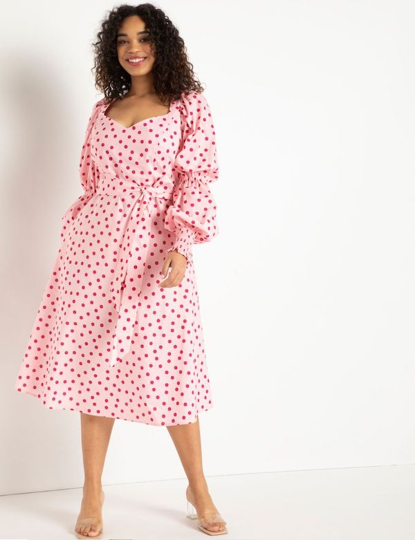 A model wearing a plus-size puff-sleeve dress in pink and red.