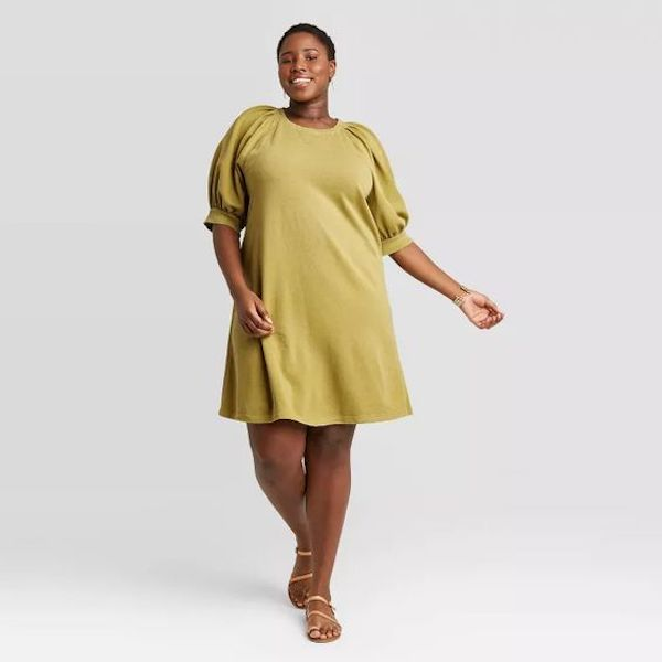 A model wearing a plus-size puff-sleeve dress in green.