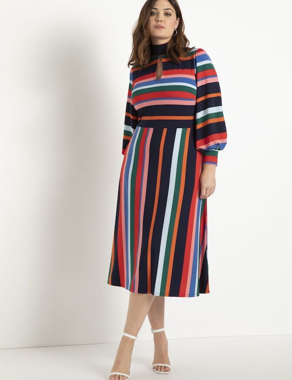 A model wearing a plus-size puff-sleeve dress in multi-color stripe.