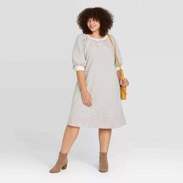 A model wearing a plus-size puff-sleeve dress in gray.