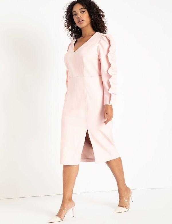 A model wearing a plus-size ruffle dress in light pink.