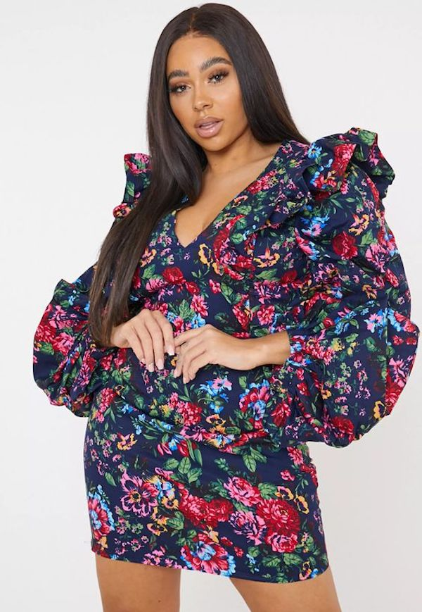 A model wearing a plus-size ruffle dress in floral print.