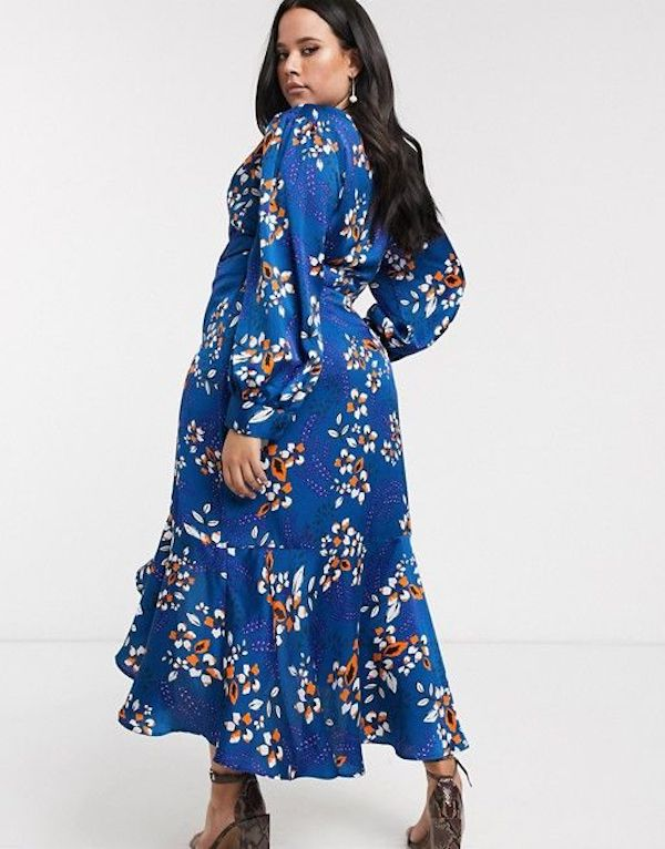 A model wearing a plus-size ruffle dress in blue floral print.