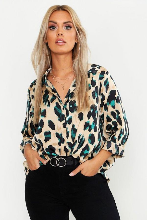 A model wearing a plus-size satin button down in leopard print.