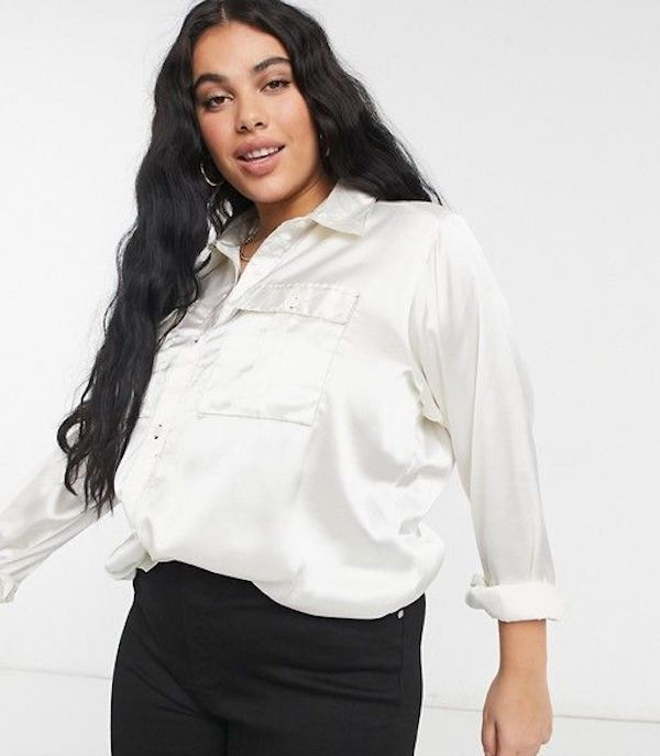 A model wearing a plus-size satin button down in white.