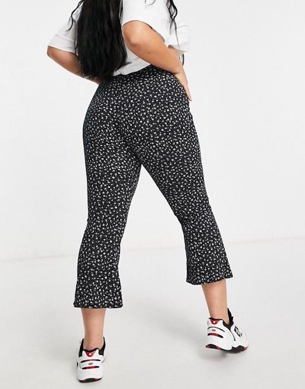 A model wearing a pair of plus-size floral print pants.