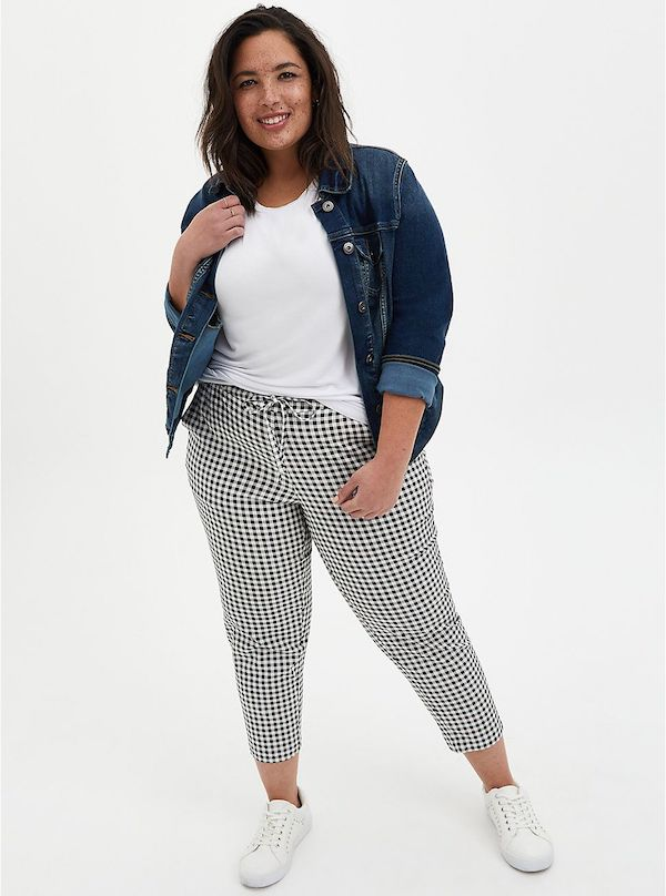 A model wearing a plus-size pair of gingham pants.