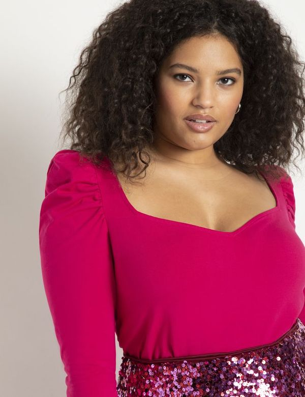 A model wearing a puff-sleeve pink top from ELOQUII.