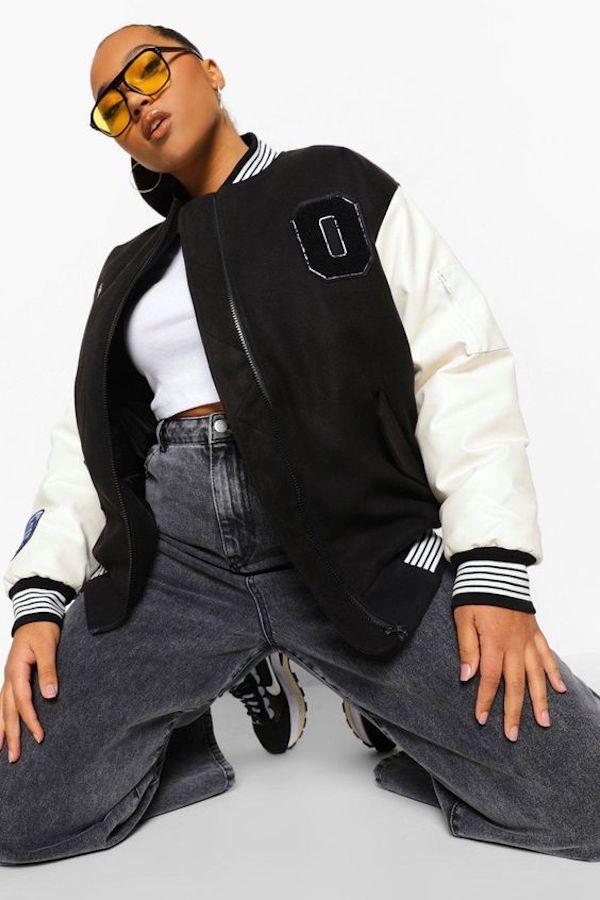 A model wearing a plus-size varsity jacket.