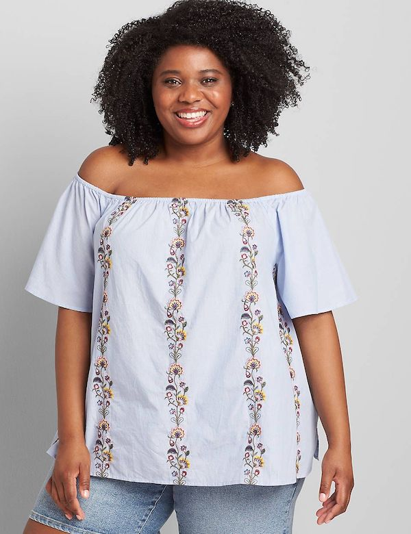 A model wearing a plus-size embroidered top.