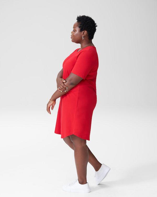 A model wearing a plus-size red dress.