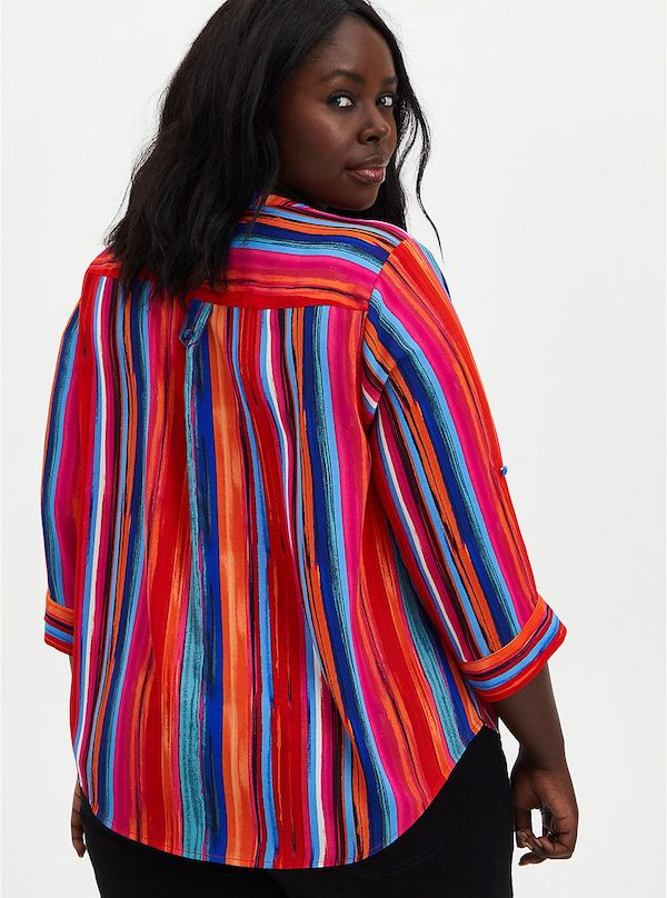 A model wearing a plus-size rainbow top.
