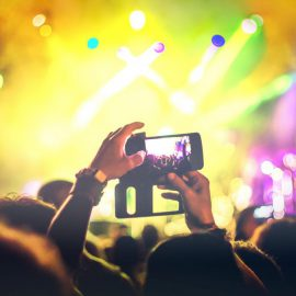 unrecognisable people recording a music concert with mobile