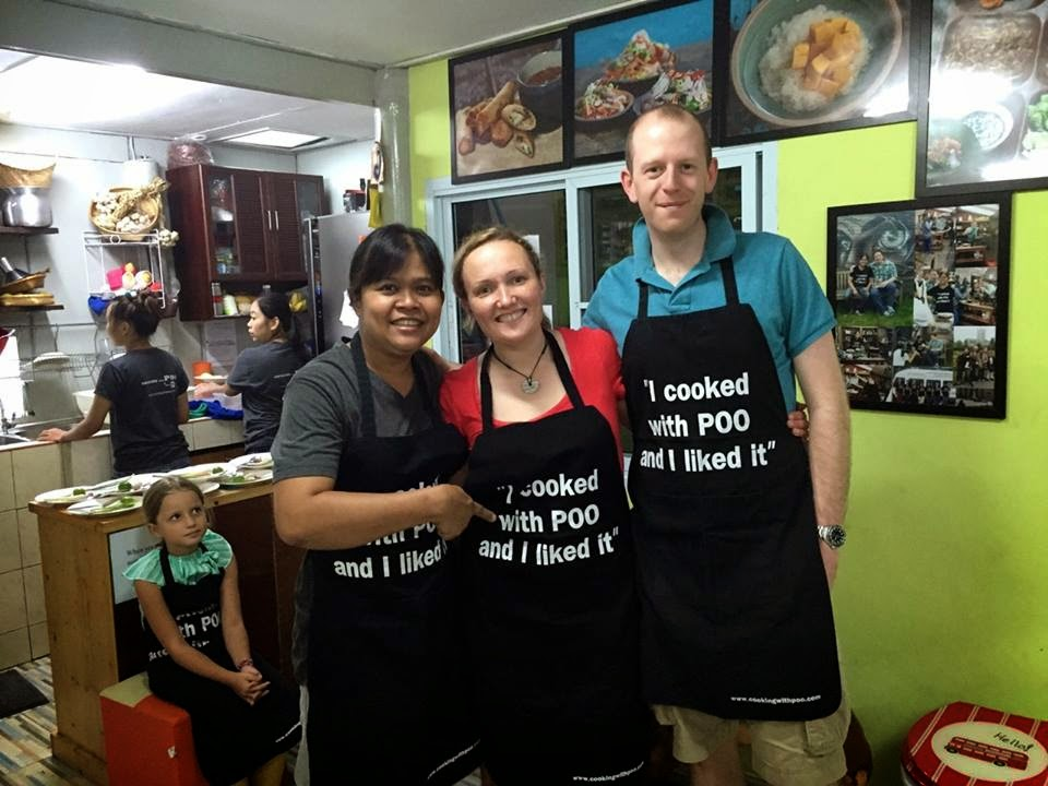 """Photo of Doug and me with Poo, wearing an apron that says """"I cooked with Poo and I liked it"""""""