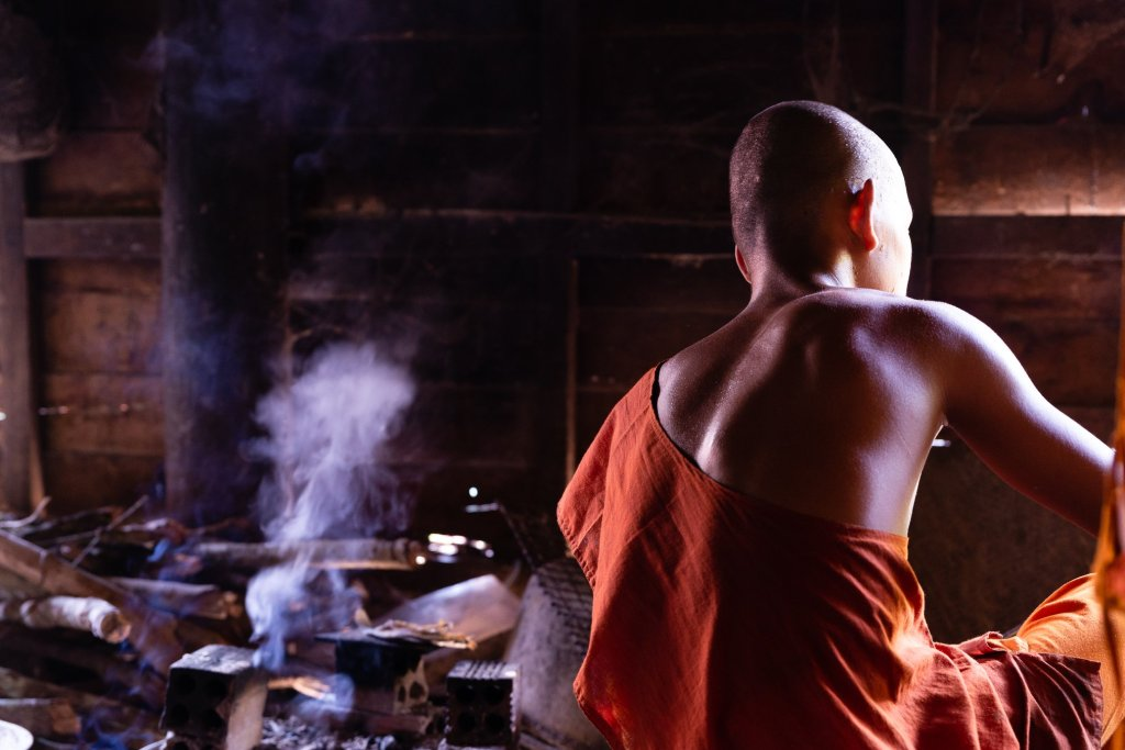 Photo of a monk sitting on the floor next to the fire where lunch is being prepared