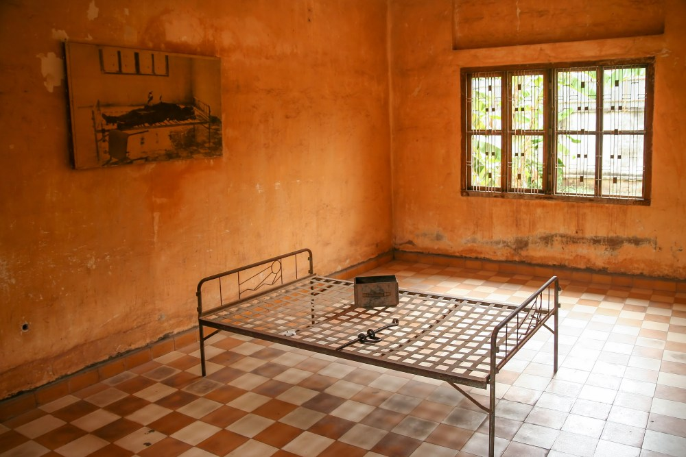 A classroom turned into a cell. The image on the wall depicting the gruesome scene the army walked into, finding a dead prisoner chained to his torture bed. A quarter of the Cambodian population was killed by Pol Pot