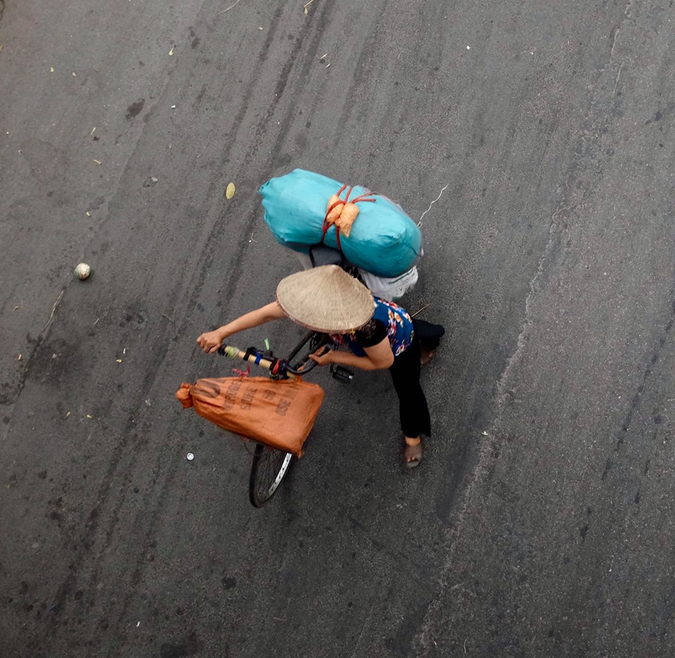 Photo of a lady pushing her bike taken directly from above