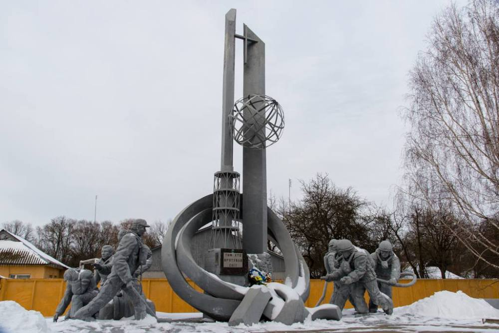 Image of a monument constructed to commemorate the firefighters that lost their lives during the Chernobyl disaster. The image shows stone firefighters carrying hoses.